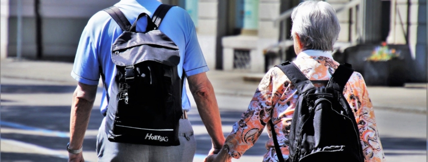 Senior couple with backpacks walking on the street