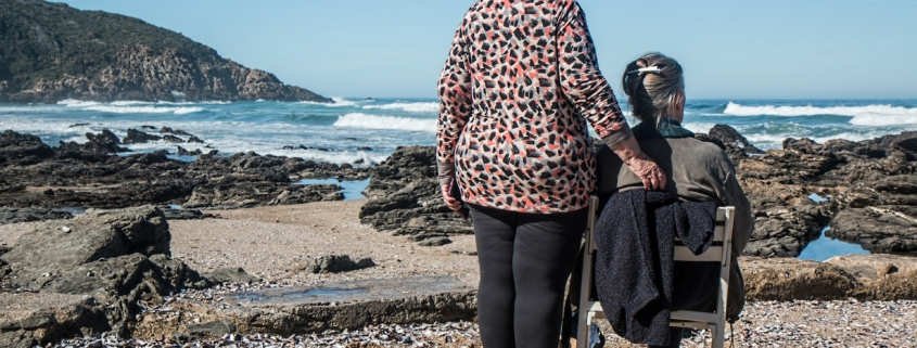 Senior woman with dementia sitting on a chair and her caregiver by the sea