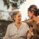Joyful adult daughter greeting happy surprised senior mother in garden