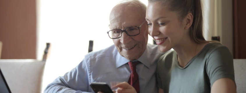 Young positive lady showing photos on smartphone to senior man while sitting at laptop